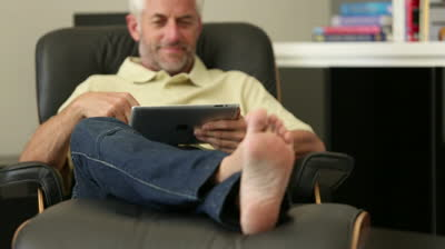 stock footage man relaxing with his tablet sitting in recliner chair in living room resized 600